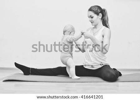 young mother does physical exercises together with her baby - stock photo