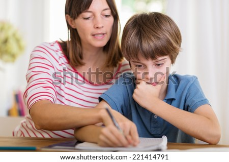 Young mother doing homework with her son pointing to something written in his notebook as he stares thoughtfully at the page - stock photo