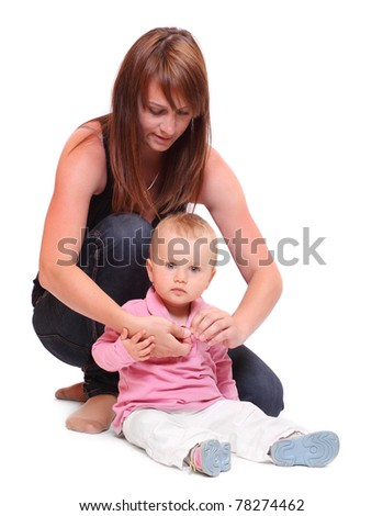 Young mother dressing her baby. - stock photo