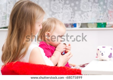 Young mother eat chocolate with adorable daughter in kitchen