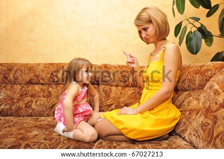 Young mother educating her little daughter at home on sofa - stock photo