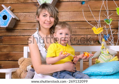Young mother embracing her little son and sitting on bench indoors - stock photo