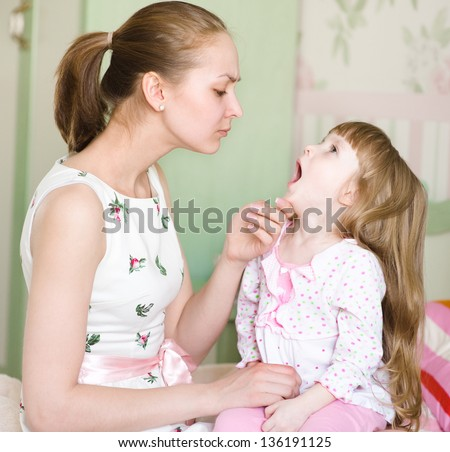 young mother examining little girl's throat - stock photo