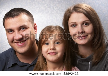 Young mother, father, and daughter over light defocused background