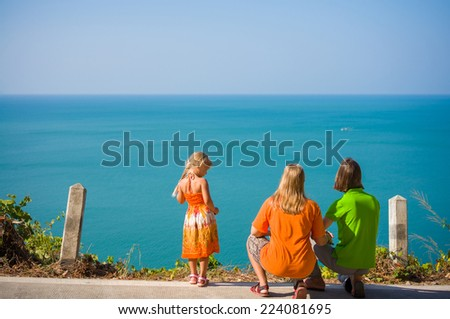 Young mother, father crouch and daughter stay on mountain road along tropical island beach and look at ocean - stock photo