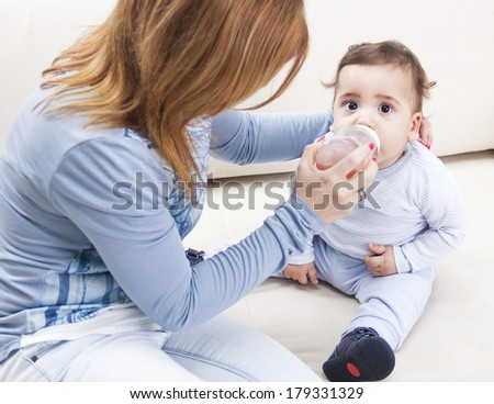 Young mother feeding baby at home - stock photo