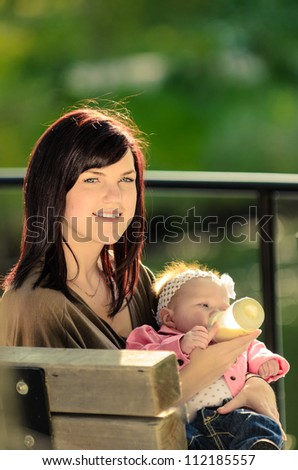 Young mother feeding baby in an outdoor park
