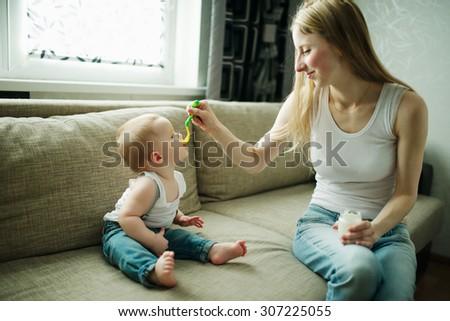 young mother feeding baby with a spoon - stock photo