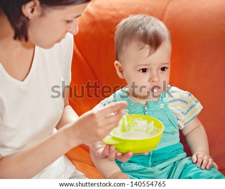 young mother feeding her infant - stock photo