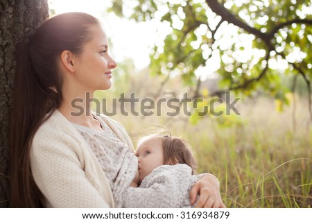 young mother feeding toddler outdoors, soft focus - stock photo