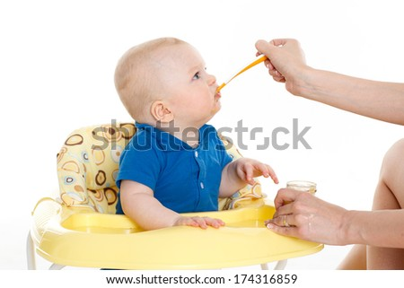 Young mother feeds  her baby on a white background. Happy family. - stock photo
