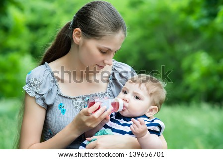 Young mother feeds her baby with milk from bottle - stock photo