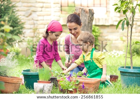 Young mother gardening in front or back yard  with her two cute little children - stock photo