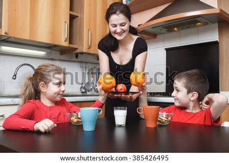 young mother give orange fruits to her daughter and son in the kitchen - stock photo