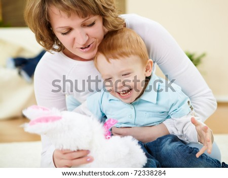 young mother having fun with her little son at home on the floor
