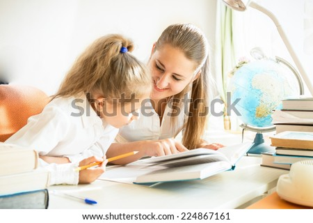 Young mother helping daughter with homework - stock photo
