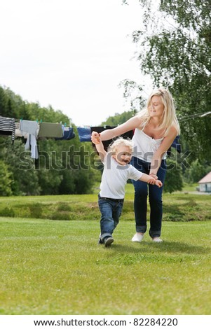 Young mother helping her little boy walk - stock photo