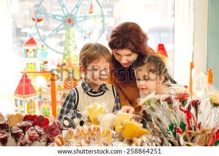Young mother her son and  daughter choosing sweets in the candy store. Happy children having fun - stock photo