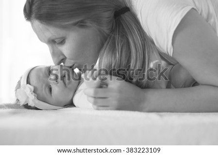 Young mother hold and kiss her newborn baby