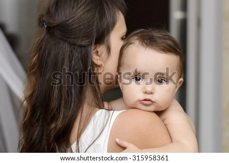 young mother holding a baby in her arms - stock photo