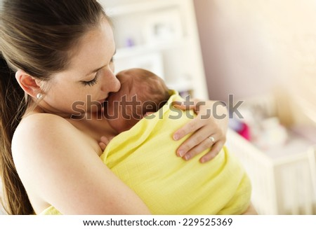 Young mother holding and kissing her newborn baby girl at home - stock photo