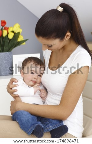 Young mother holding baby boy on lap, embracing tenderly. - stock photo
