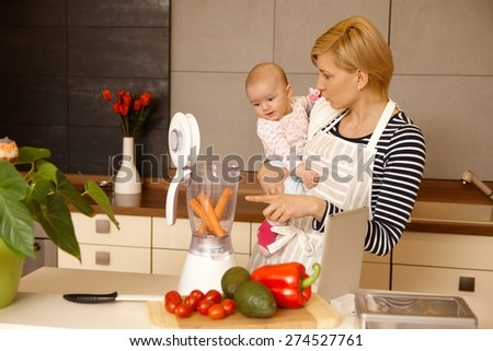 Young mother holding baby girl in arms, preparing food together in kitchen. - stock photo