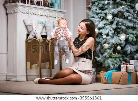 Young mother holding baby son and smiling while sitting beside Christmas tree - stock photo
