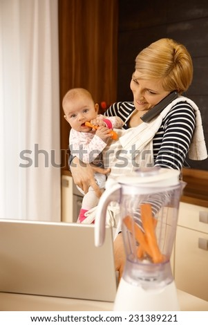 Young mother holding baby, talking on phone, using laptop. - stock photo