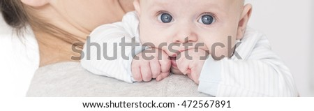 Young mother holding blue eyed baby sucking thumb