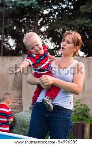 Young mother holding grumpy crying toddler boy outdoors in the garden. - stock photo