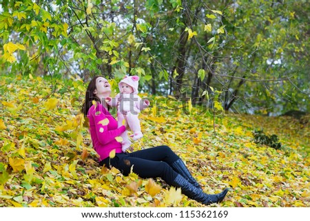 Young mother holding her baby catching falling autumn leaves - stock photo