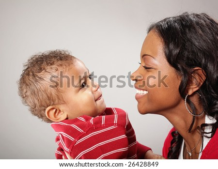 Young mother holding her cute little baby - stock photo