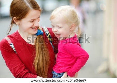 Young mother holding her cute toddler girl on a summer day outdoors - stock photo