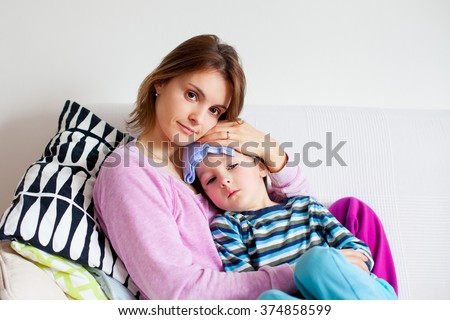 Young mother, holding her little sick boy, wet cloth on his forehead - stock photo