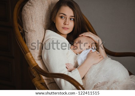 young mother holding her newborn baby sitting in armchair