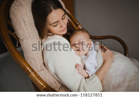 young mother holding her newborn baby sitting in armchair - stock photo