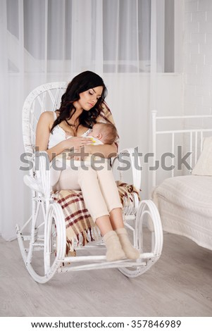 Young mother holding her newborn child. Mom nursing baby. Woman and new born relax in a white bedroom with rocking chair. Family at home. - stock photo