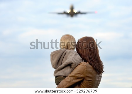 Young mother holding her toddler son with airplane on background  - stock photo