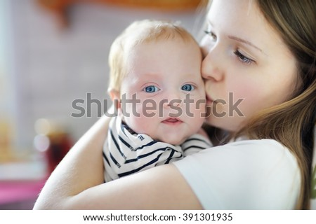 Young mother holding his sweet newborn baby - stock photo