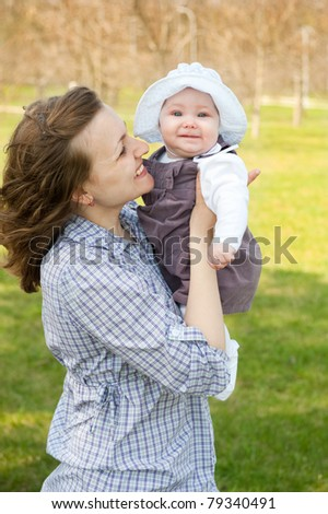 Young mother holding little baby daughter outdoors
