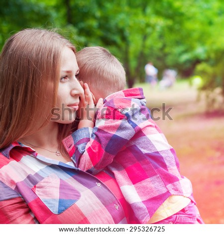Young Mother Holds her Son on Hands in the Summer Park. Toned Effect - stock photo