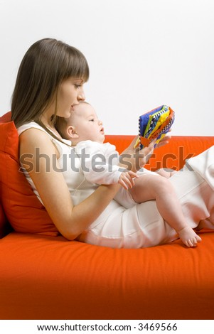 Young mother hugging baby boy. Sitting on orange couch. Reading to him book. Side view - stock photo