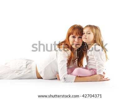 Young mother hugging her daughter and looking in camera on white background.