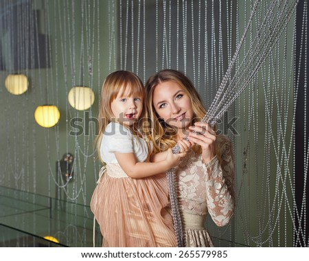 Young mother hugging her daughter, closeup portrait in the home for interior. The concept of family happiness. - stock photo