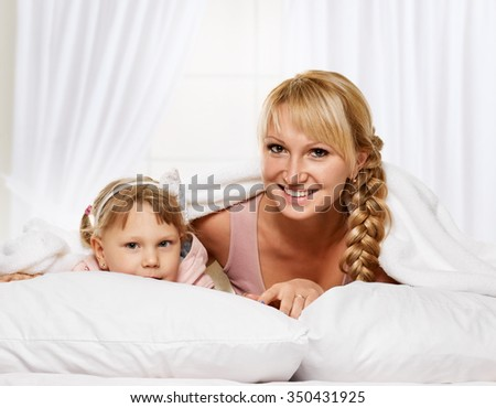 Young mother hugging her daughter on light window background - stock photo