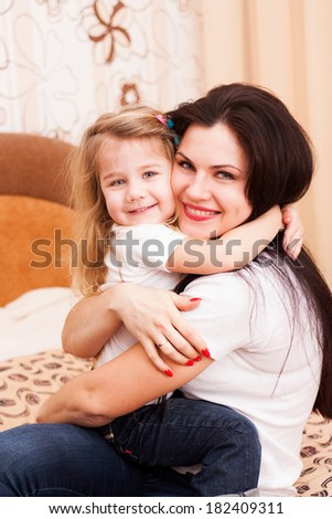 Young mother hugs her cute little daughter. Family portrait.