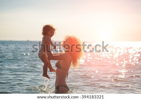 Young mother in bikini standing swimming and playing with male child boy in sea or ocean water sunny day outdoor on natural background, horizontal picture - stock photo