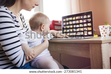Young mother in home office with computer and her daugher - stock photo