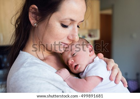 Young mother in kitchen holding her son in her arms
